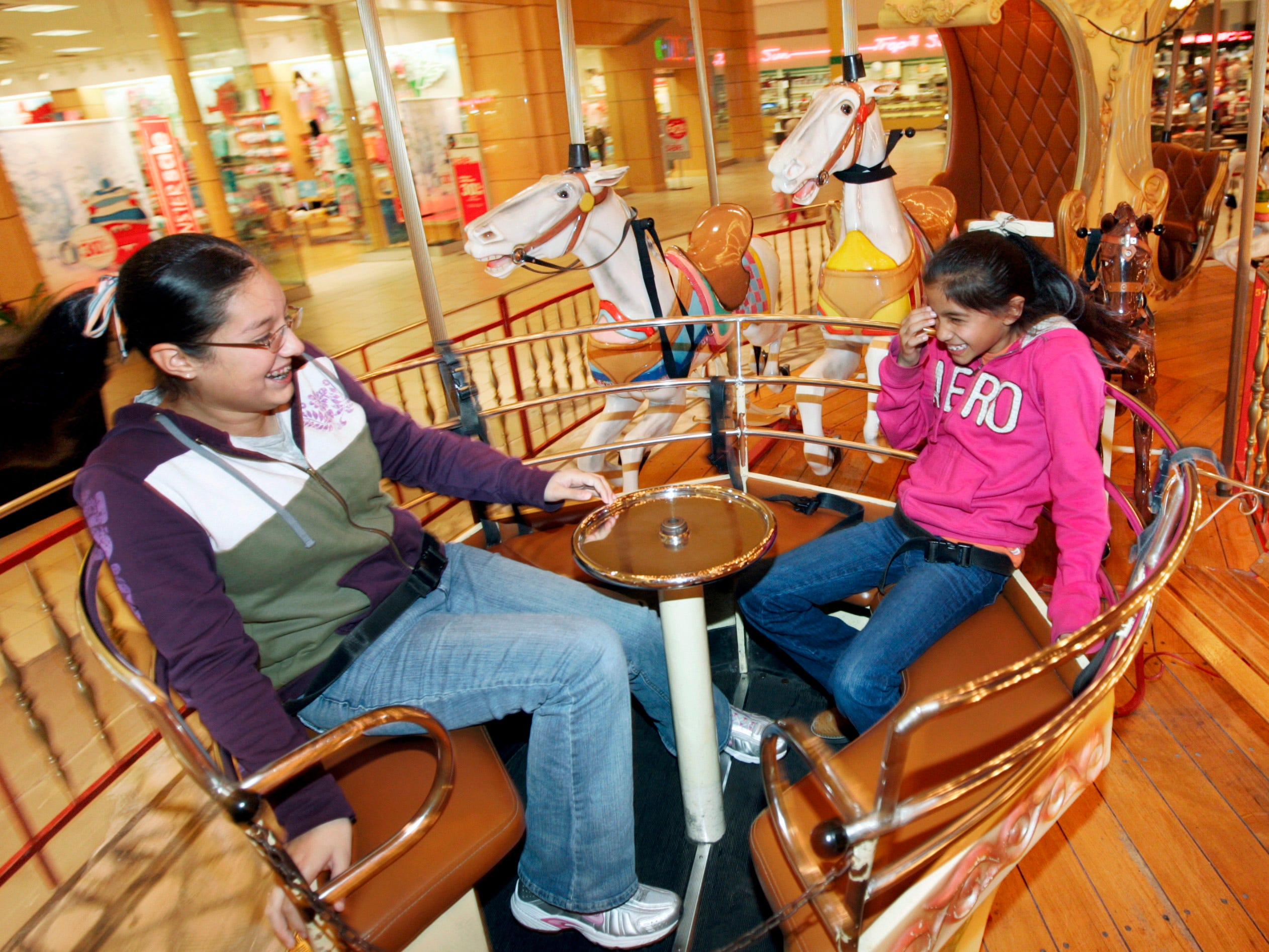 Desiree Trevino, 12, (left) and her 10-year-old sister Lauren Castellano, both from Refugio, laugh as they twirl around in one of the spinning tubs Wednesday, Jan. 14, 2009, on the carousel at La Palmera mall in Corpus Christi.