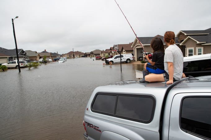 Jen and 4-year-old TJ Miller fish off the of the top of a tuck parked in their driveway on Nunavut Drive after heavy rains over night flooded the area on Friday, May 10, 2019.