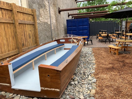 Once you get your craft beer, wine or cocktail, you can find a table or settle into this refurbished boat from the Camden Shipyard & Maritime Museum.
