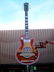 In this June 26, 2018 photo a worker puts finishing touches on the giant guitar outside the Hard Rock casino in Atlantic City. New jersey gambling regulators have fined a technology company $25,000 for enabling a Nevada man to gamble online on the Hard Rock's web site in violation of state law requiring internet gamblers to be within New Jersey's borders.