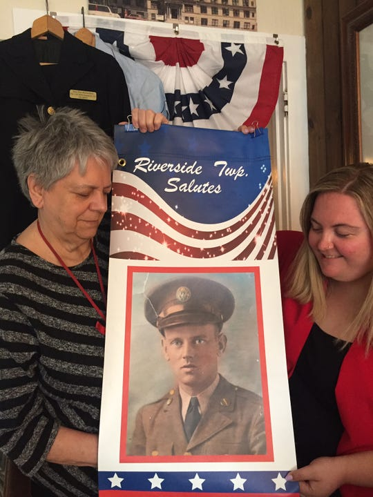 Banners like this one will hang from lamp posts in Riverside beginning on Memorial Day weekend to  honor war veterans who lived in town. This photo depicts William Carl Jr., a World War II Army and D-Day veteran. He was the father of Riverside Historical Society President Alice Smith (left) , who is holding the banner with society secretary Brittany Rae.