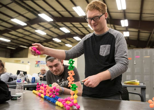 Todd Bauer helps Kyle Brown put together a train statue using connection blocks at First Capital Enterprises on May 7, 2019, in Chillicothe, Ohio.