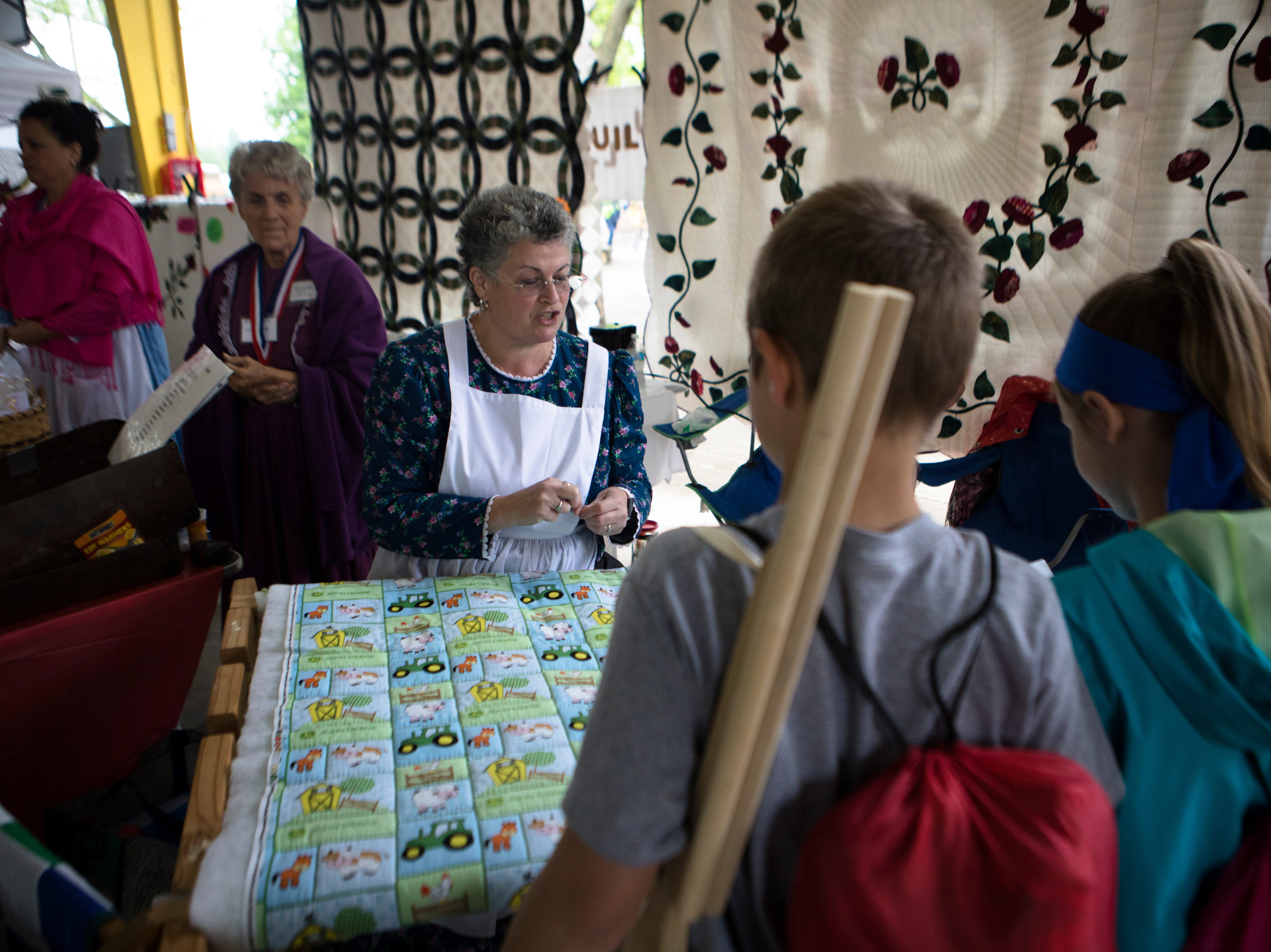 Susan Anderson teaches children how to quilt during the 50th annual Appalachian Festival on Friday, May 10, 2019, At Coney Island in Cincinnati.