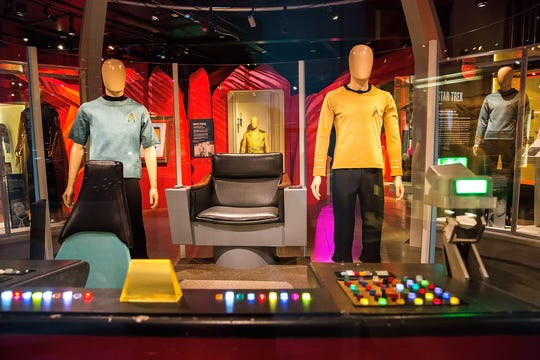 The 'Star Trek' exhibit at Henry Ford Museum features a recreation of the bridge from the original series, including original costumes worn by DeForest Kelley (Dr. McCoy) and William Shatner (Captain Kirk), the original navigation console from the show, and a replica of the captain's chair.