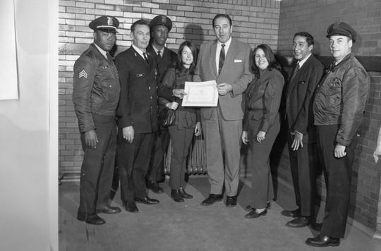 Officer Judith Dowling, third from right, helped originate Police and Youth in Sports, which became the Detroit Police Athletic League. In this undated photo, then-Detroit Police Chief Johannes Spreen, center, honors the program. Second from left is Lt. Leon Shanks, another key to starting the youth program.