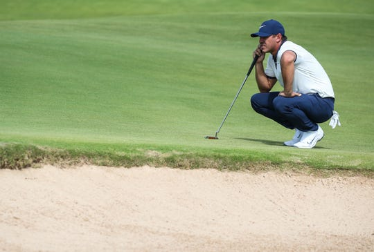 Brooks Koepka lines up to putt on the first green.