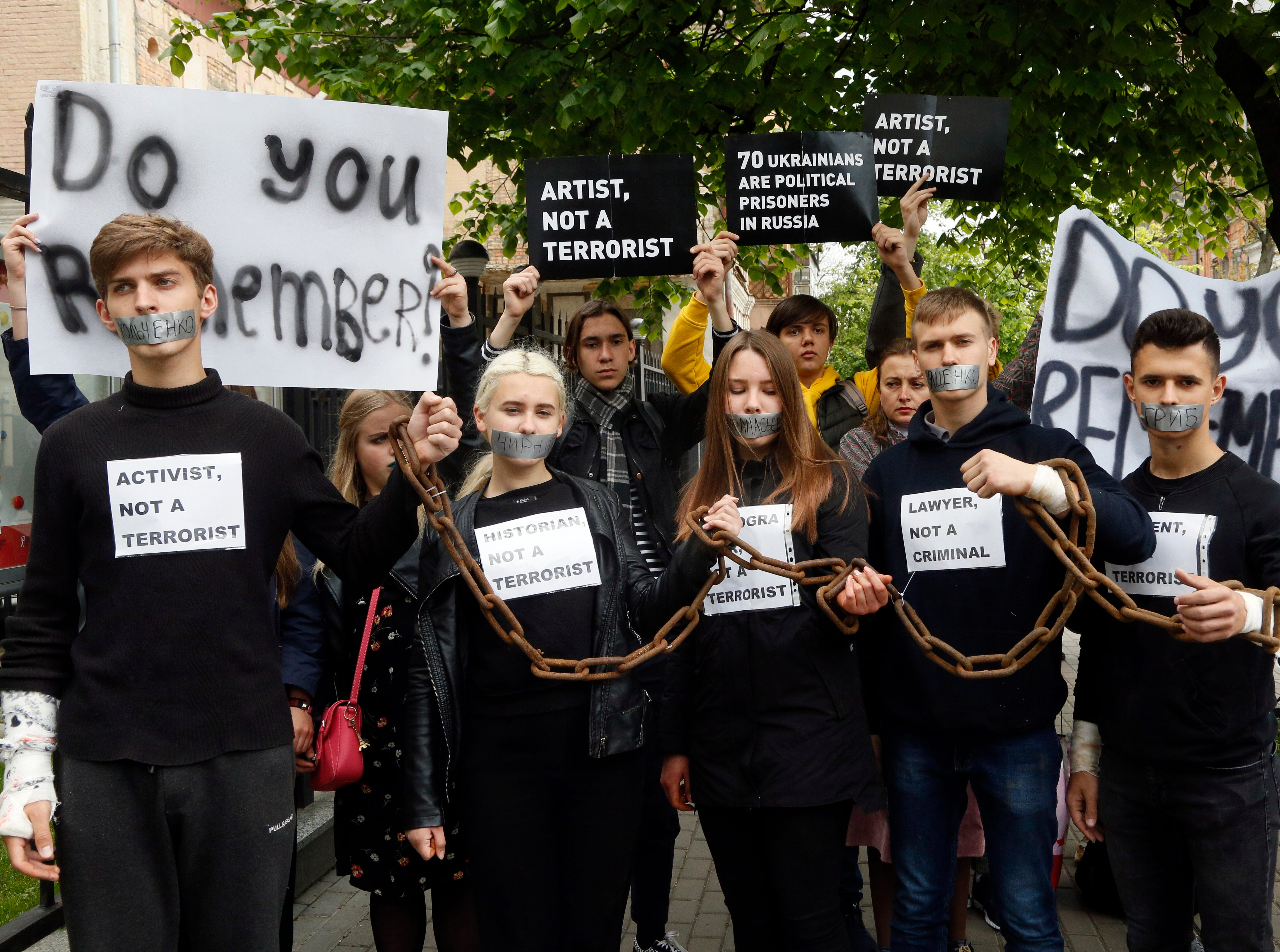 Activists, with their mouths covered by band-aids, stand chained together, in central Kiev, Ukraine, Friday, May 10, 2019. The activists performed a symbolic march to the embassies of the European Council member states and handed over the letters to highlight the fact that Ukrainian political prisoners are still being kept in Russian jails.