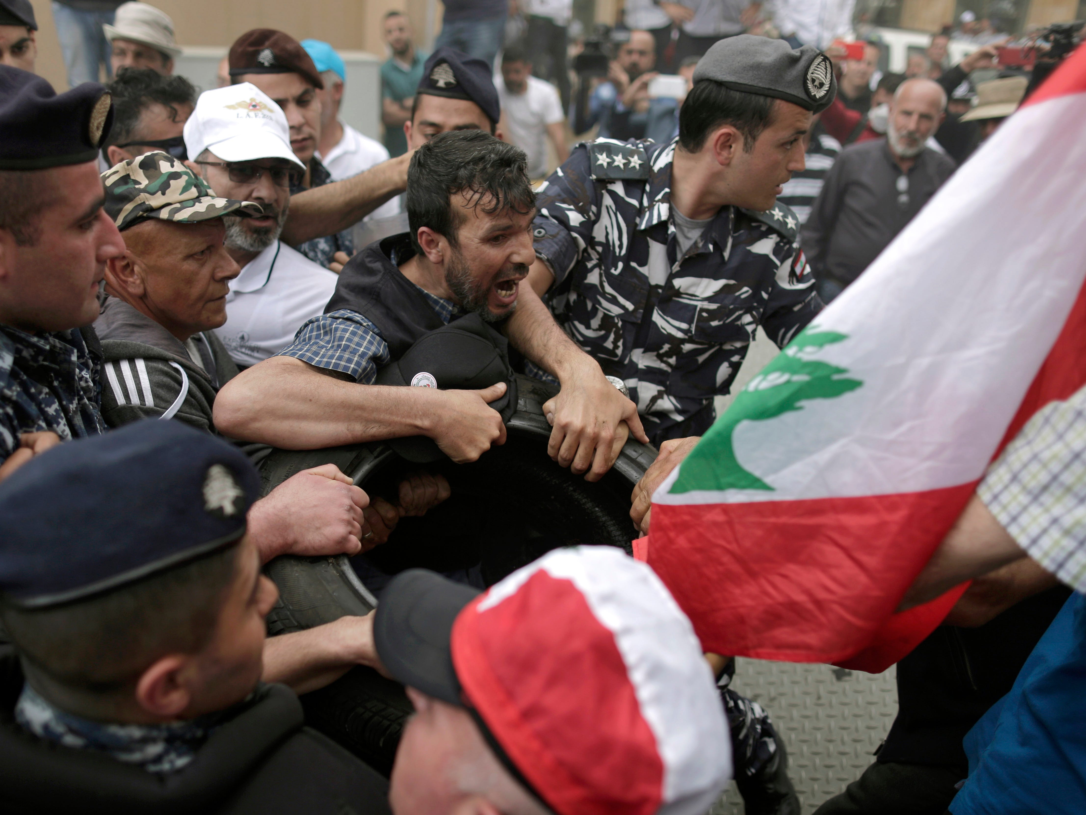 Police scuffle with Lebanese retired soldiers during a protest in front of the government building during a cabinet meeting to discuss an austerity budget, in Beirut, Lebanon, Friday, May 10, 2019. Dozens of Lebanese military and security veterans burned tires and shouted angrily outside government offices on Friday, their second protest in less than two weeks amid fears a proposed austerity budget may affect their pensions and benefits.