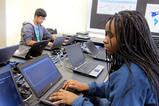 In this March 13, 2019, photo, Bennett High School students Galib Ovik and Rachael Miller work on re-imaging laptops in a school computer lab in Buffalo, N.Y. They are among student technicians trained by Buffalo Public Schools to help maintain school-issued devices.