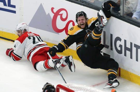 Boston Bruins' David Pastrnak, right, is upended after a check by Carolina Hurricanes' Sebastian Aho (20).