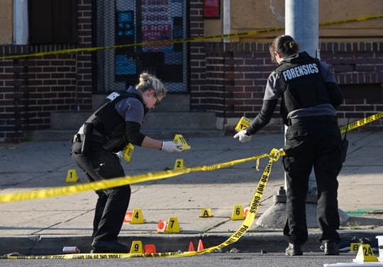 Baltimore police forensics officers  investigate the scene of a shooting in Baltimore on Sunday, April 28, 2019. A gunman fired indiscriminately into a crowd that had gathered for Sunday afternoon cookouts along a west Baltimore street, killing one and wounding seven.