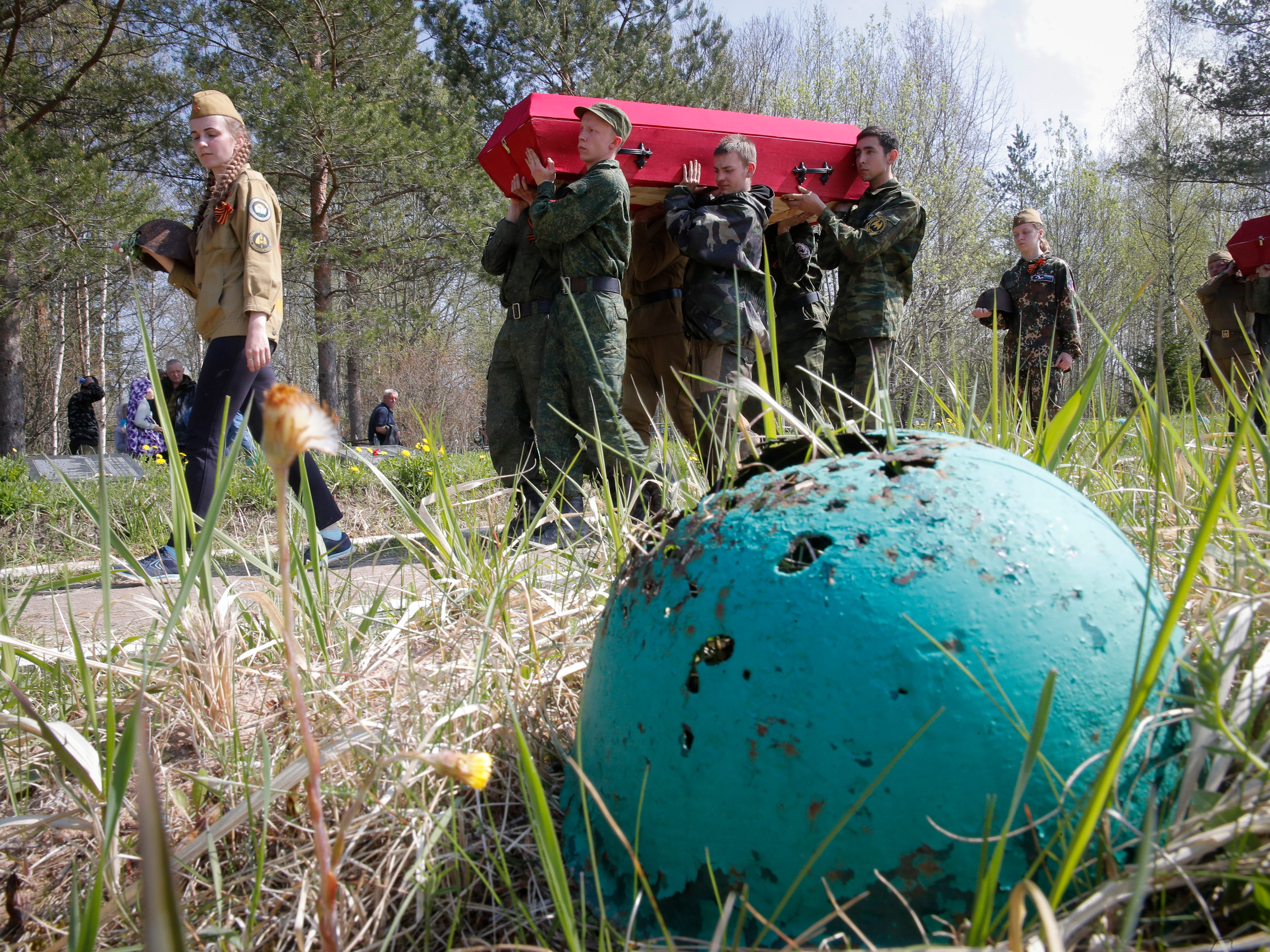 Members of volunteer search teams carry coffins with remains of Soviet soldiers killed during World War II, during a reburial ceremony in a memorial cemetery at Chudskoy Bor, 100 km (62 miles) South from St.Petersburg, Russia, Friday, May 10, 2019. People came to a World War II battleground outside St. Petersburg this week to bury the remains of 92 Soviet soldiers recovered by volunteer search teams.
