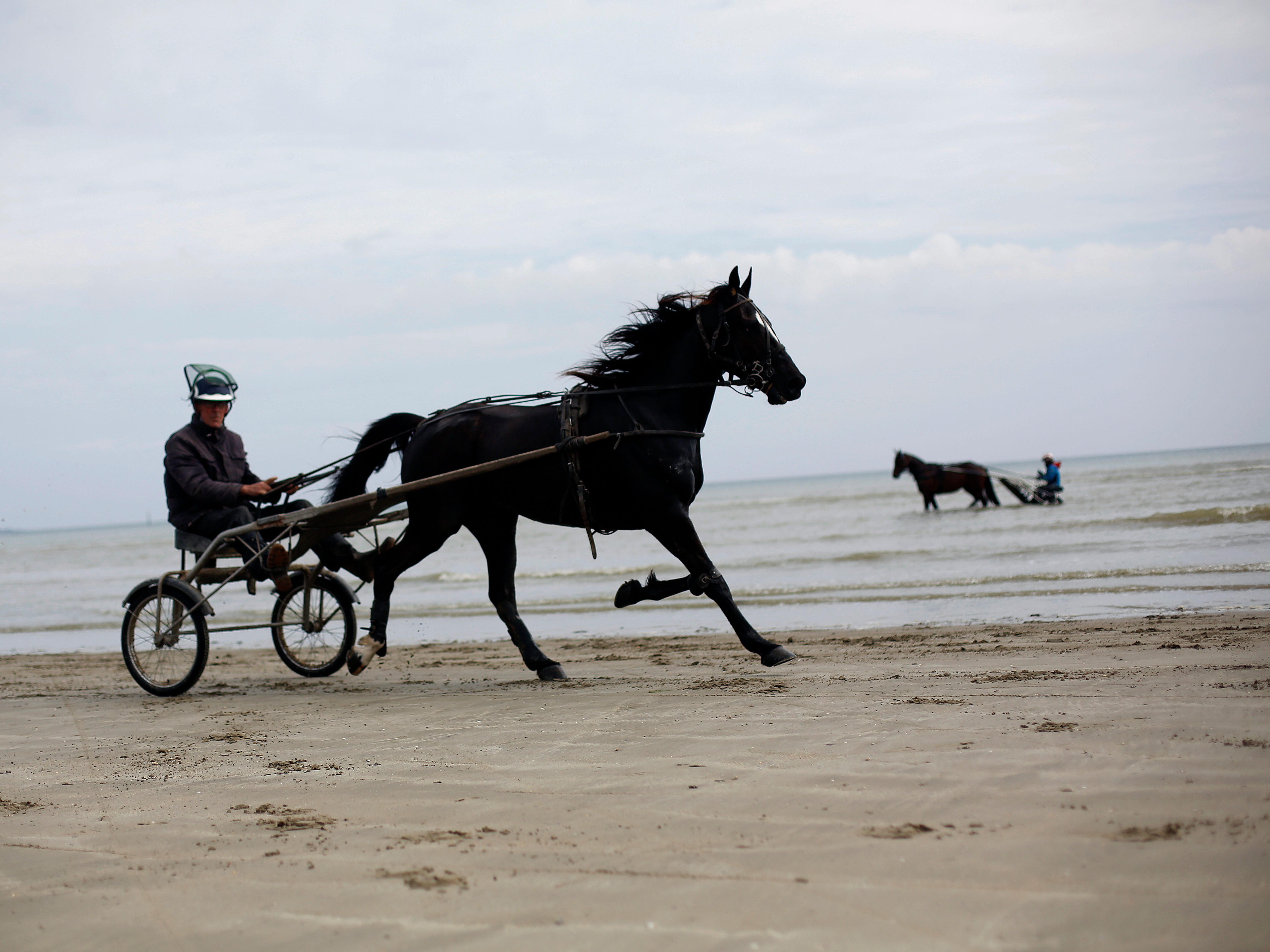Riders take their horse and buggy on Utah Beach, in Normandy, western France, Friday, May 10, 2019.