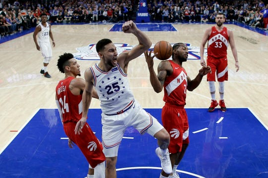 Philadelphia 76ers' Ben Simmons (25) reacts after dunking the ball between Toronto Raptors' Danny Green (14) and Kawhi Leonard (2) during the second half.