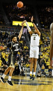 Western Michigan's Michael Flowers (12) defends a 3-point attempt by Michigan's Jordan Poole (2) this past season.