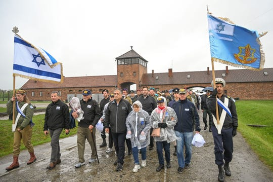 """Holocaust survivor Sophie Tajch Klisman (wearing a red scarf), 89, of Detroit, and fellow survivor Gizella Mann, 89, of Israel visit the former Auschwitz concentration camp recently during their participation in the Friends of the Israel Defense Forces (FIDF) """"From Holocaust to Independence"""" mission to Poland and Israel."""