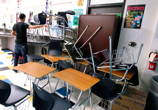 In this Jan. 22, 2013, file photo, a student helps block the classroom door with furniture during a mock lockdown drill at Moody High School in Corpus Christi, Texas.