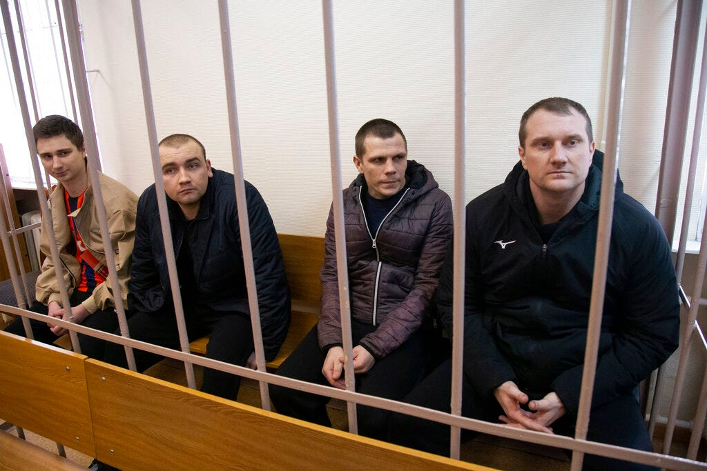 In this April 17, 2019, file photo, Ukrainian sailors sit in a cage in a courtroom in Moscow, Russia. Ukraine is demanding the immediate release of its sailors and ships, arguing that failure to do so would breach the country's rights. Russia argues that the sovereignty rights Ukraine claims in the case don't apply because they are covered by a military exception.