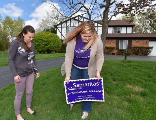 Foster parent Sarah Sporny, left, and Samaritas Foster Care Case Worker Sara Dingman, right, of Flushing, put a Samaritas sign in Sporny's front yard. May is Foster Care Month in the State of Michigan.