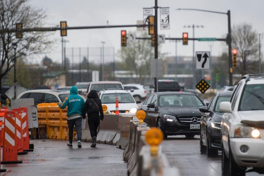 Pedestrians use a temporary walkway as traffic uses a Westbound lane on the opposite side of a barricade on Thursday, May 9, 2019, on West Elizabeth Street, between South Shields Street and City Park Avenue, in Fort Collins, Colo.