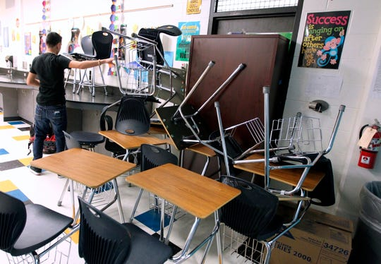 FILE - In this Jan. 22, 2013, file photo, a student helps block the classroom door with furniture during a mock lockdown drill at Moody High School in Corpus Christi, Texas.  The actions of students who died tackling gunmen at two separate U.S. campuses a week apart have been hailed as heroic. A majority of school districts have now embraced such an approach, with experts saying educators need to give staff and students as many options as possible in the worst-case scenario. (Rachel Denny Clow/Corpus Christi Caller-Times via AP, File)