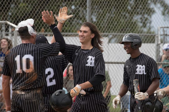 Mariner's Gavin Walker gets a high five after hitting a solo home run in the bottom of the fifth against Island Coast during the District Class 6A-11 championship game Friday.