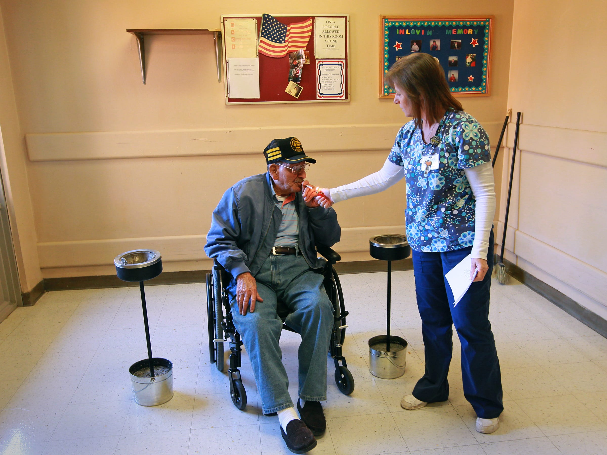 """Ernest Butler, who served in the U.S. Army starting in 1945, gets help lighting a cigarette from Angie Brock, assistant activities director, takes smoke breaks in a designated room at Richard Campbell Veterans Nursing Home in Anderson. Cigarettes are handed out, one at a time by a worker, for anyone who wants to smoke. """"It helps pass time away,"""" said Butler in 2013."""