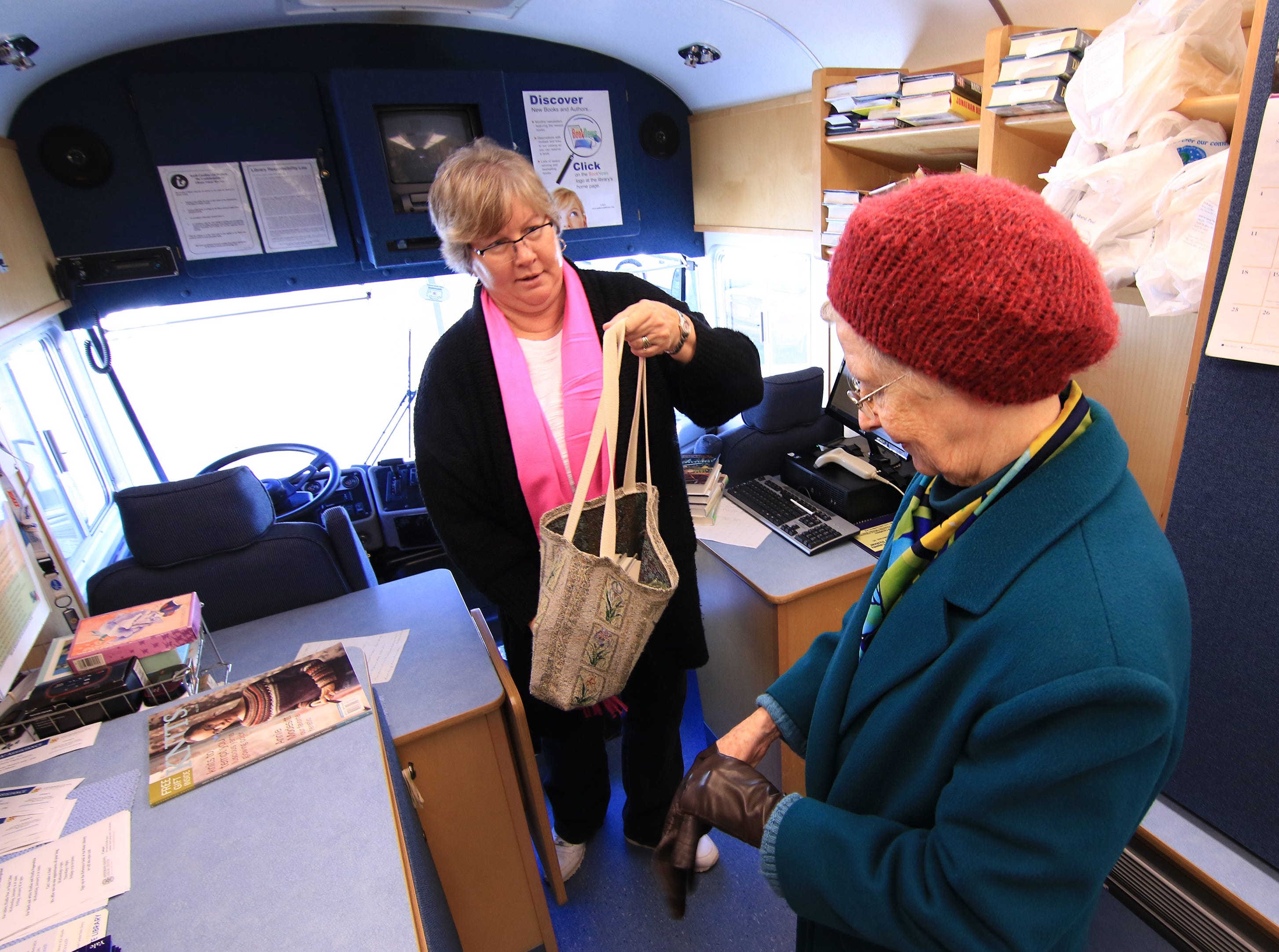 Delores Strickland, left, a librarian assistant for the Anderson County Library Bookmobile, helps B.J. Bare of Anderson with books during her stop at the Richard M. Campbell Veterans Nursing Home in Anderson. Bare said she knows the mobile truck stops in the parking lot at the home, a convenience she likes in 2015.