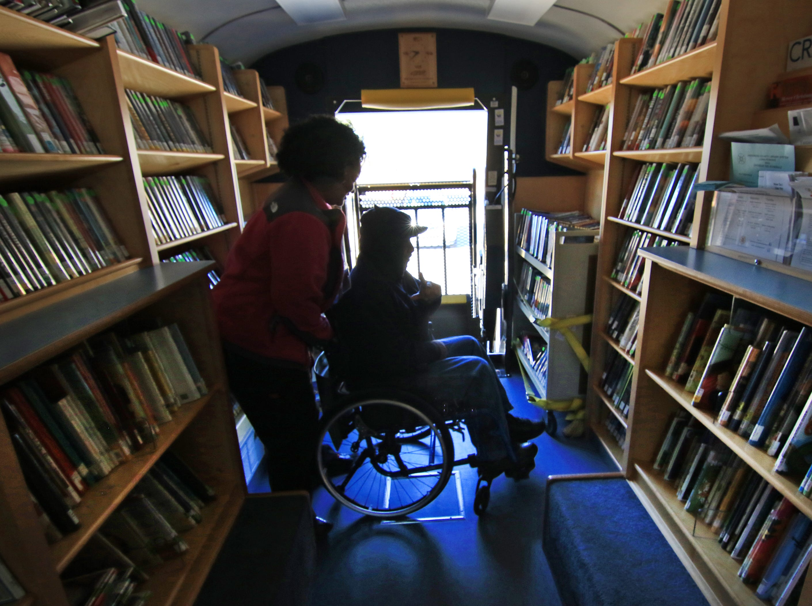Kawanna Sullivan, left, helps George Pressley, U.S. Marine Corps veteran, through the Anderson County Library Bookmobile after finding movies and books he likes, in the parking lot of the Richard M. Campbell Veterans Nursing Home in Anderson in 2015.