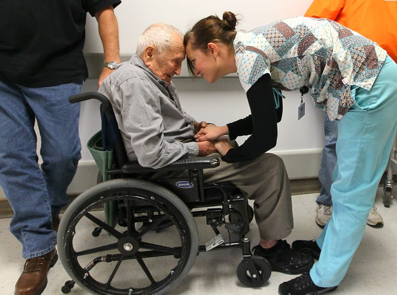 Charles Bay, a U.S. Army World War II veteran, shares a moment with Heidi Campbell, activity assistant at Richard M. Campbell Veterans Nursing Home in Anderson, while waiting in line for Thanksgiving day lunch in 2013.