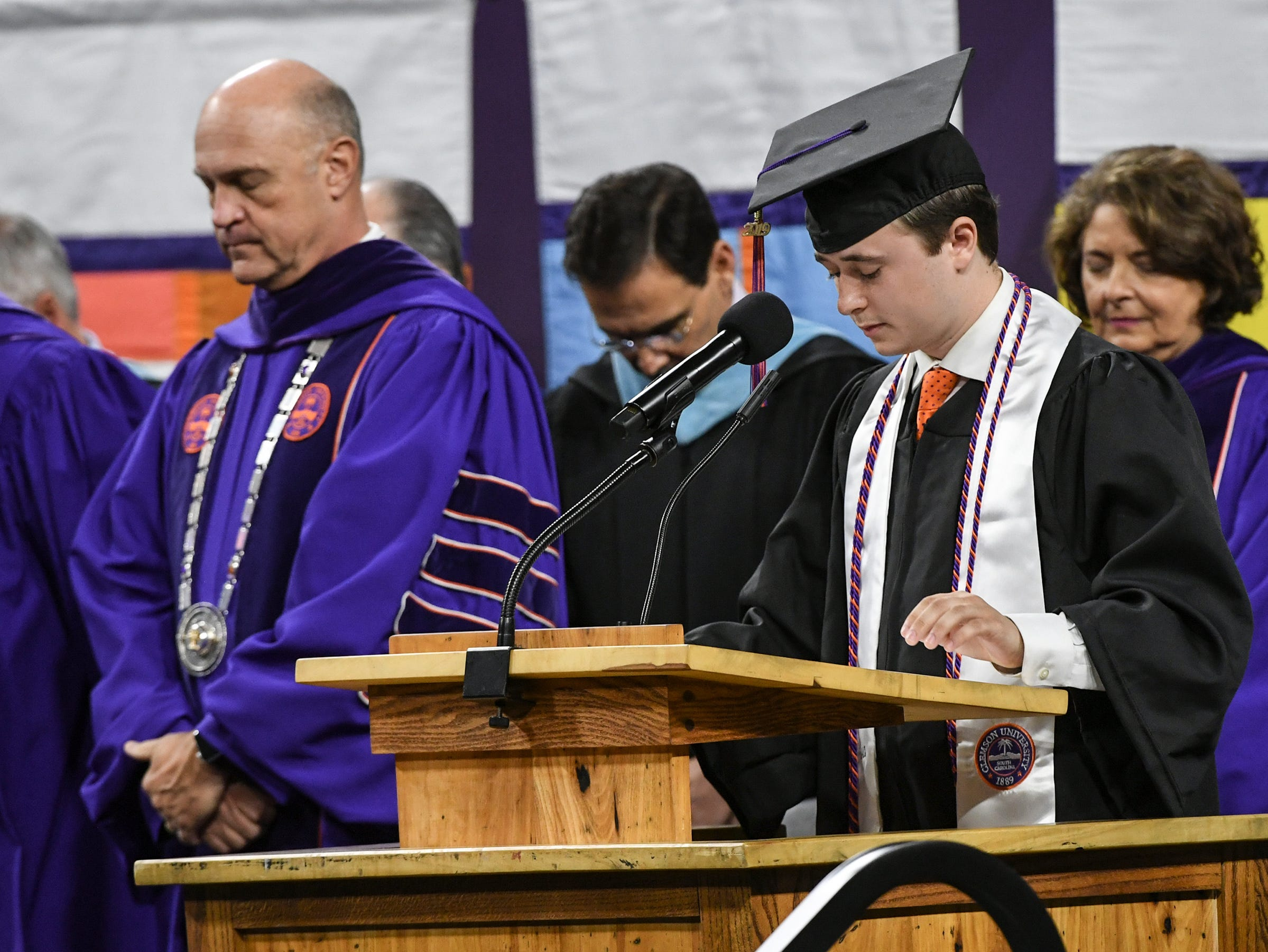 Jacob Crotts gives the invocation near President Jim Clements during Clemson University commencement ceremonies in Littlejohn Coliseum in Clemson Friday, May 10, 2019.