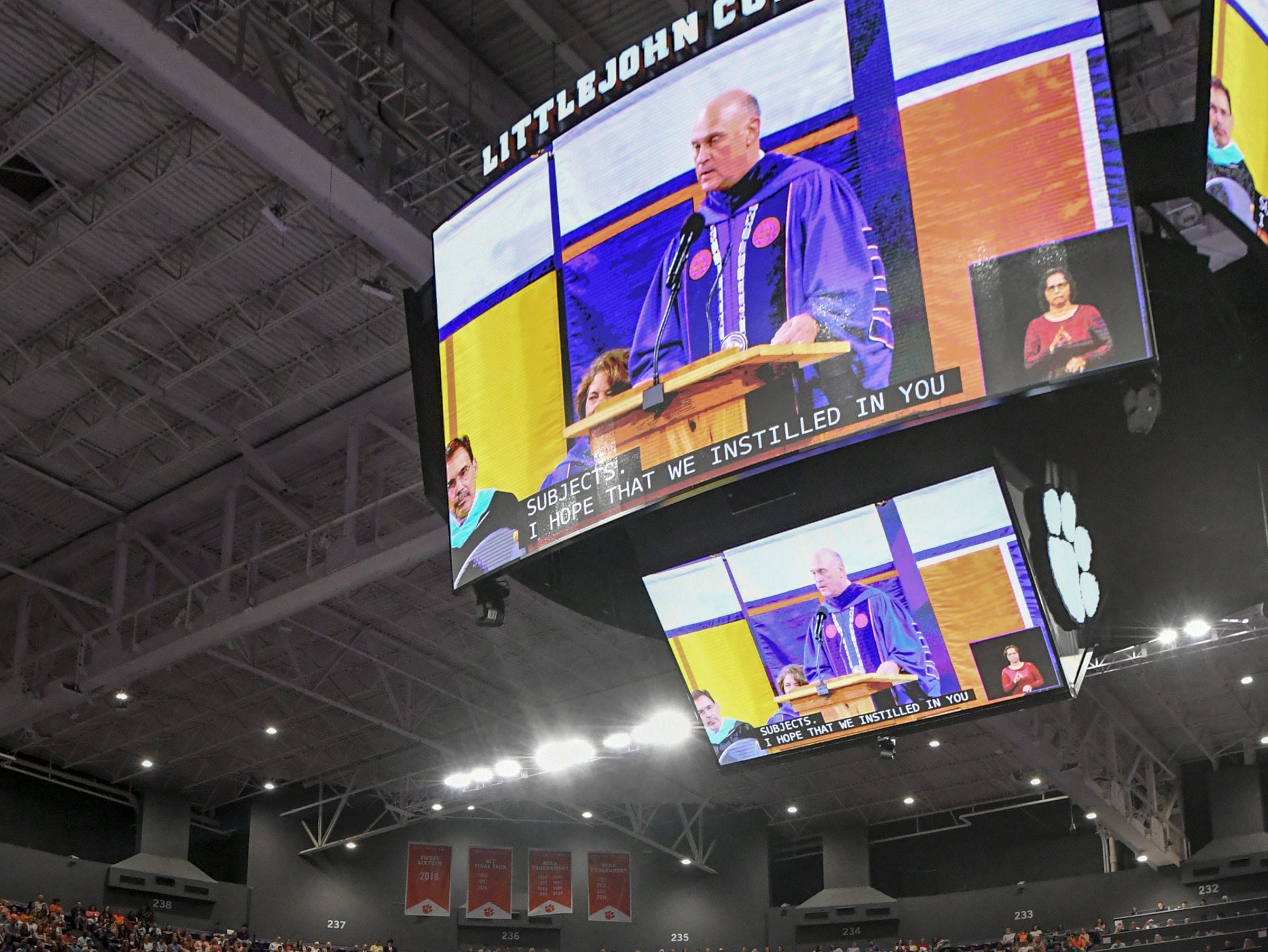 Ryan Mac Lain, seated with an orange IPTAY stoll and a former football player, joins listening to President Jim Clements make closing remarks after he earned his Bachelor of Arts in Psychology, during Clemson University commencement ceremonies in Littlejohn Coliseum in Clemson Friday, May 10, 2019.