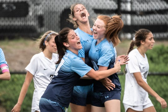 Southside Christian's Samantha Speaks, Rachel Castellani and Campbell Shubert celebrate after a goal scored against Oceanside Collegiate Friday afternoon at Irmo High School in Columbia. Southside won 6-1.