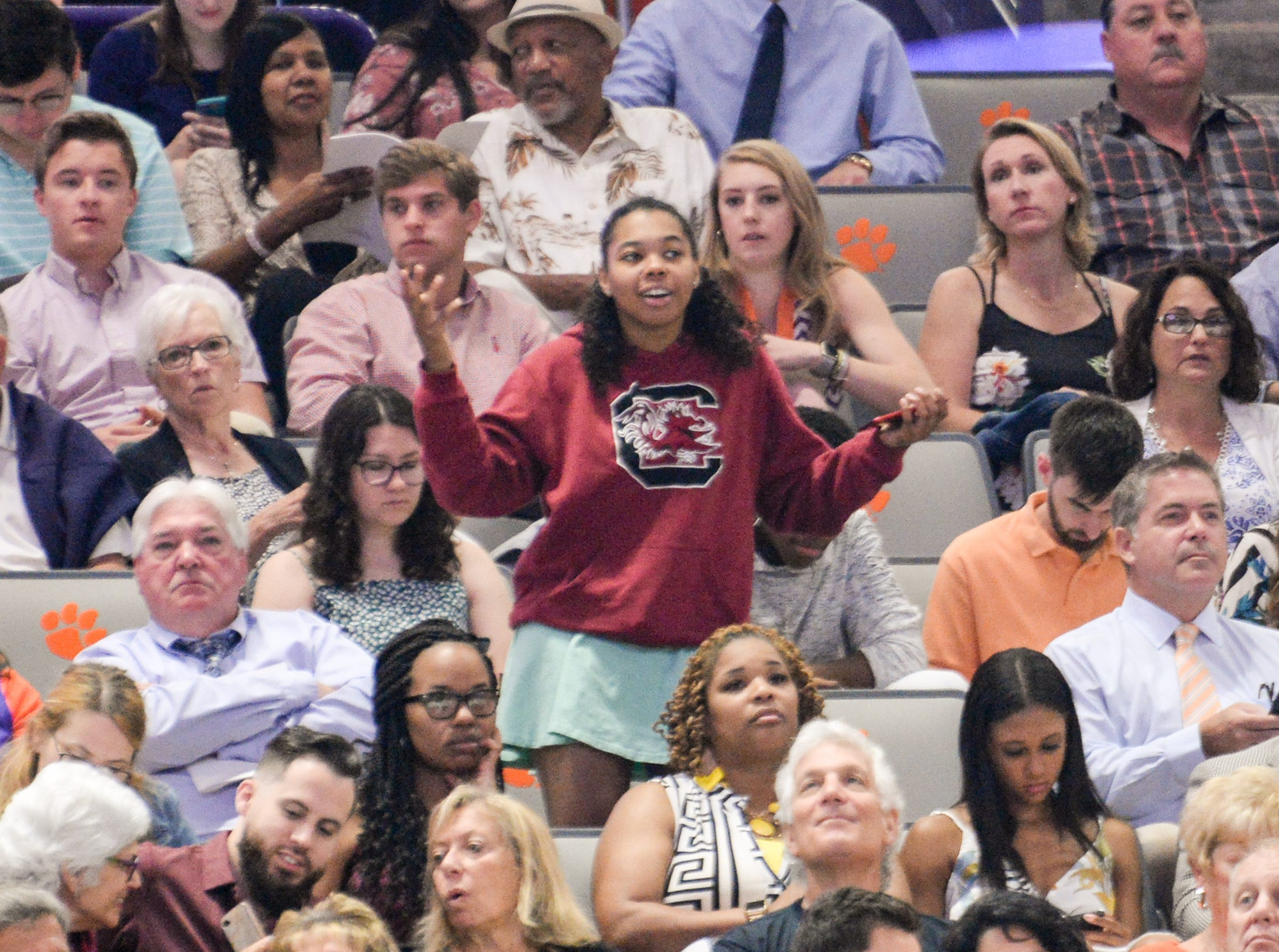 A young woman wearing a University of South Carolina sweatshirt stands up in a crowd an hour before Clemson University commencement ceremonies in Littlejohn Coliseum in Clemson Friday, May 10, 2019.