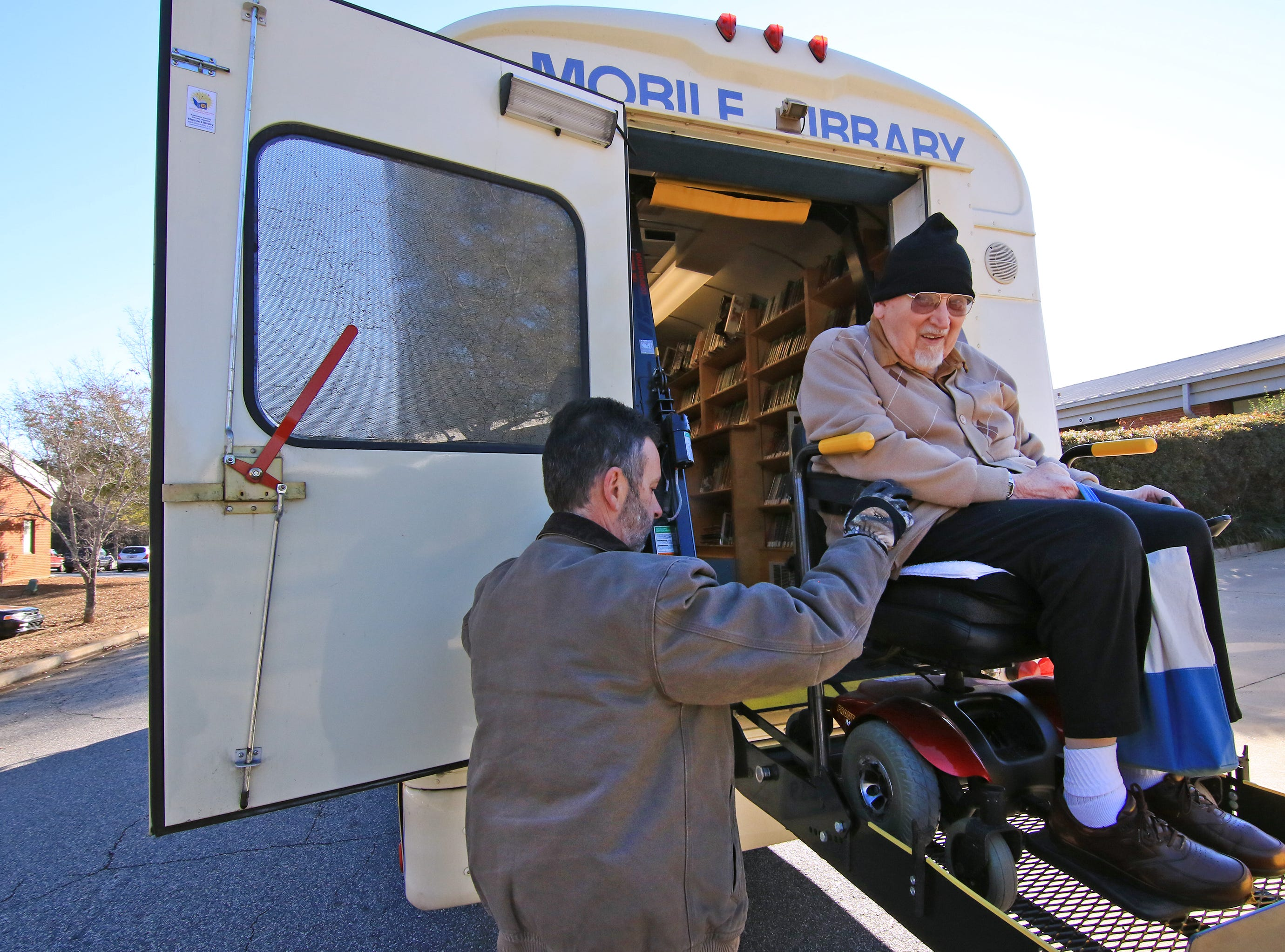 James Brissey, left, helps John Scott, U.S. Navy veteran, out of the Anderson County Library Bookmobile, at the Richard M. Campbell Veterans Nursing Home in Anderson. Scott looks forward to seeing the mobile library which brings books he is interested in 2015.