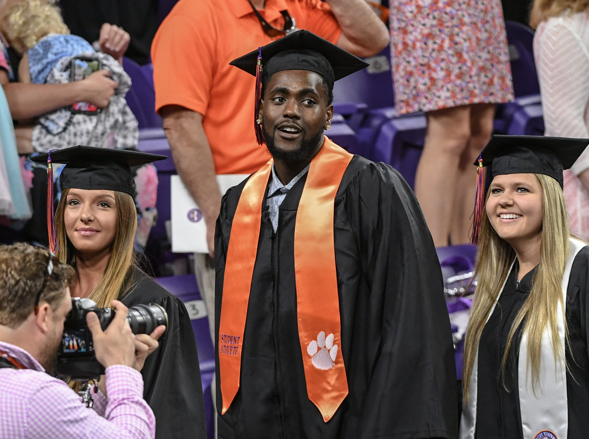Alexandria Temple, left, and Paige Timberlake, right, stand on each side of a taller graduate, former men's basketball player Elijah Thomas of Dallas, Texas during Clemson University commencement ceremonies in Littlejohn Coliseum in Clemson Friday, May 10, 2019. Thomas and his classmates all earned a bachelor of science in Parks, Recreation, and Tourism Management.