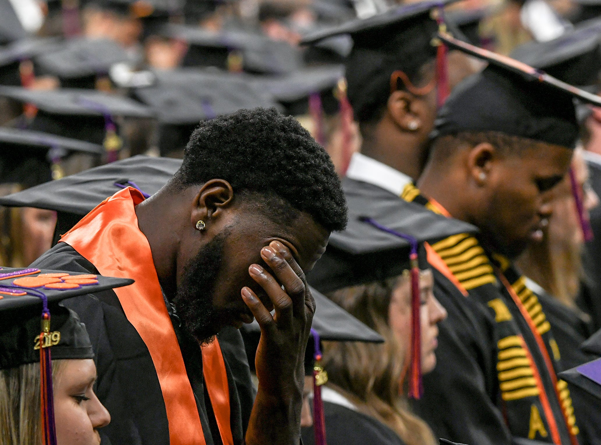 Elijah Thomas, former men's basketball player, joins other graduates with the invocation by Jacob Crotts during Clemson University commencement ceremonies in Littlejohn Coliseum in Clemson Friday, May 10, 2019.