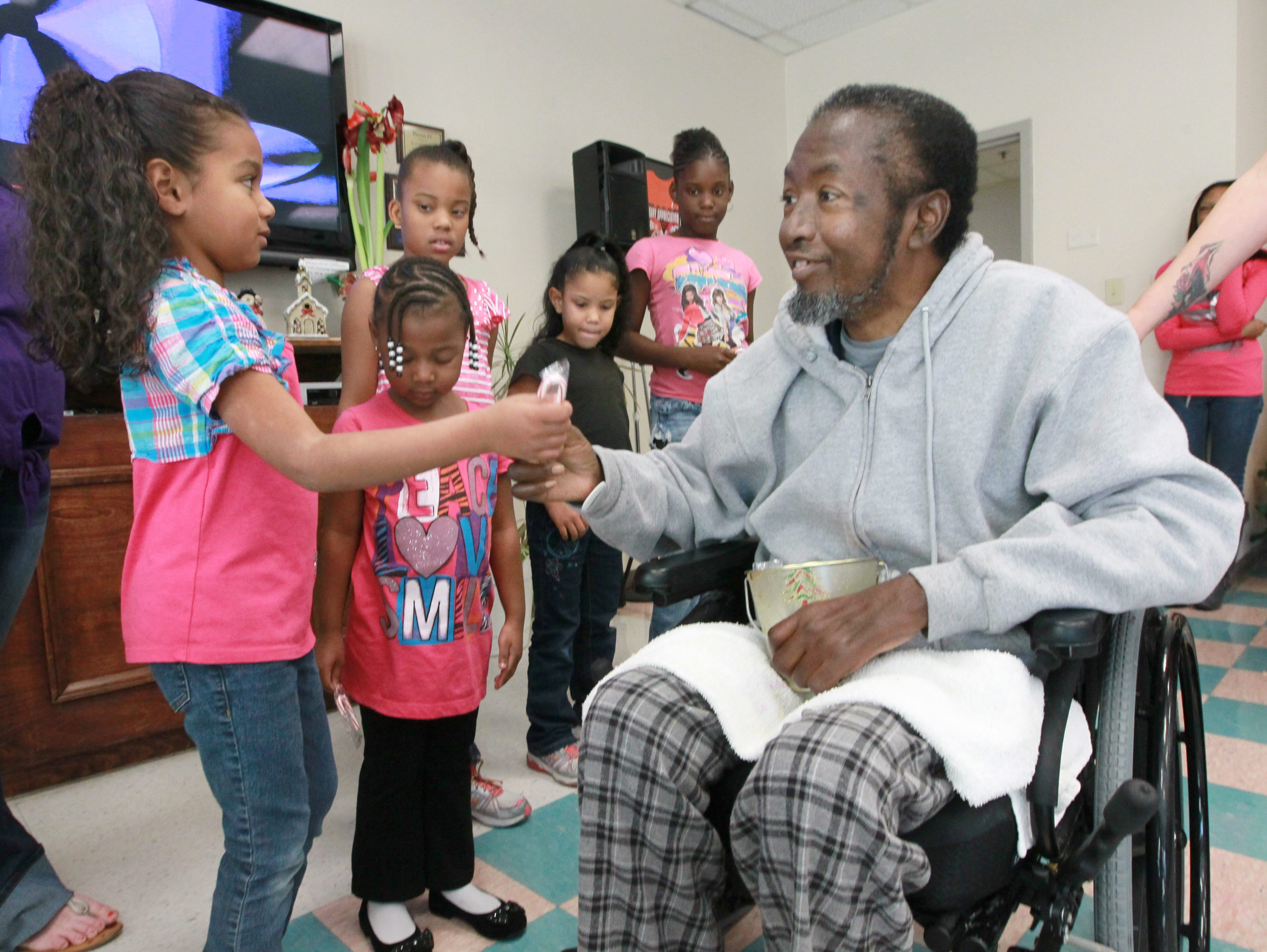 Thomas Midgette, a veteran who served in the Vietnam era with the United States Air Force, gives Ava Harsey a candy cane at Richard Campbell Veterans Nursing Home.  Girls from the group Miracles, children of single parents, also included, left of Ava, Regina Boggs, Zari Trenton, Alexis Freeman, and Aaliyah Burton in 2012.