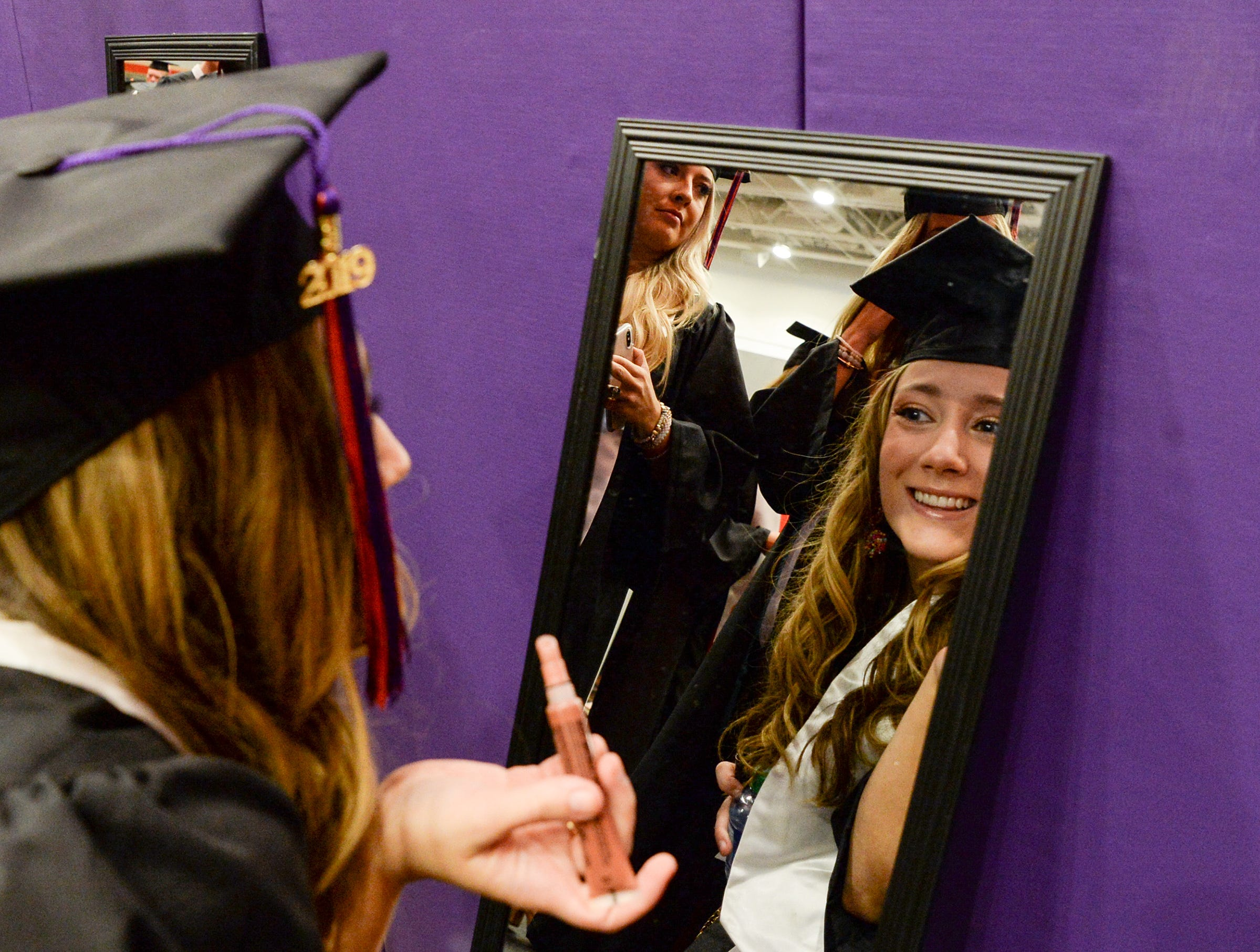 Carly Chapman of Greenville checks herself in a mirror before Clemson University commencement ceremonies in Littlejohn Coliseum in Clemson Friday, May 10, 2019.