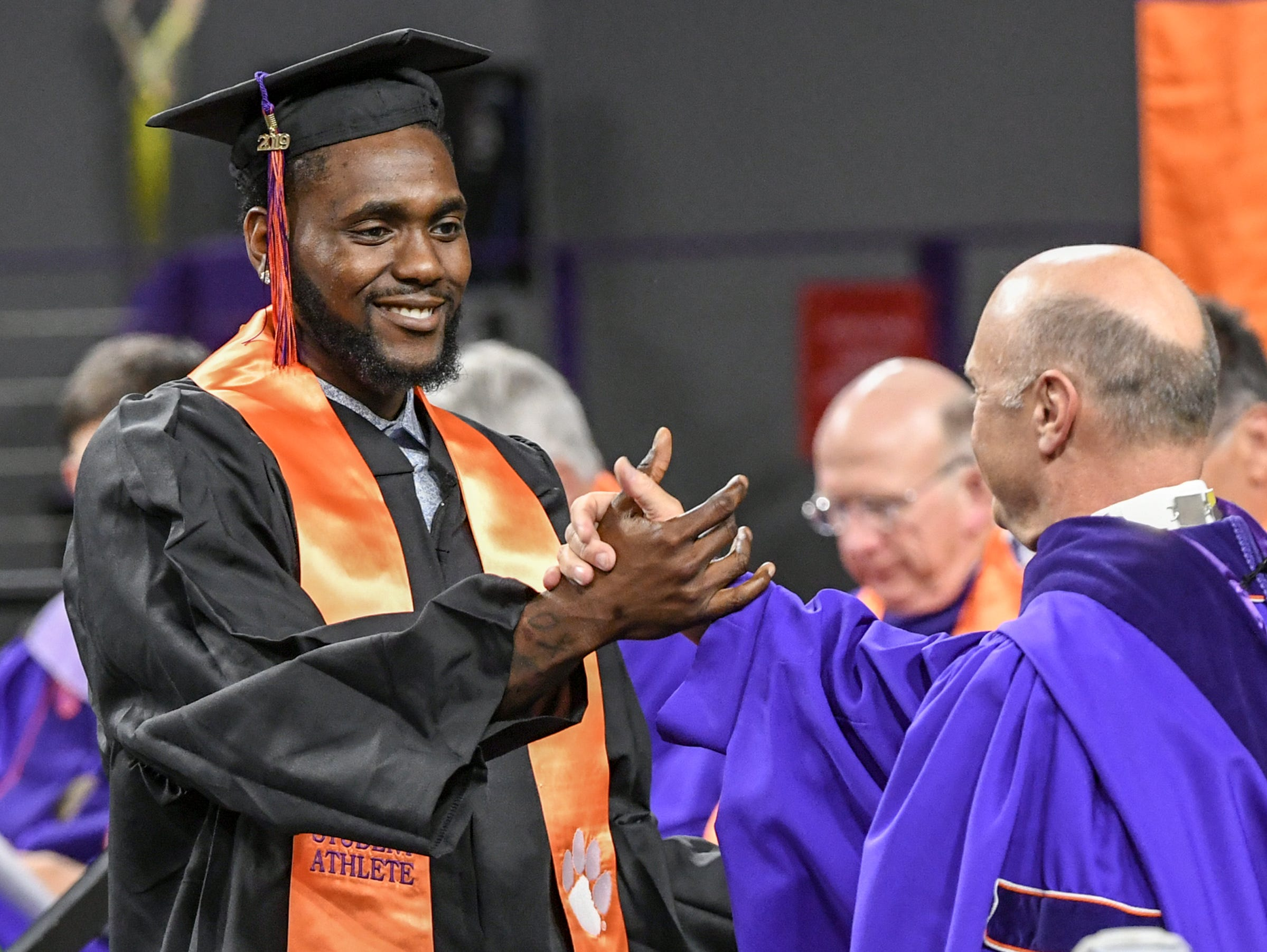 Elijah Thomas, left, a former men's basketball player who earned a bachelor of science in parks, recreation, tourism, management, shakes hands with President Jim Clements during Clemson University commencement ceremonies in Littlejohn Coliseum in Clemson Friday, May 10, 2019.