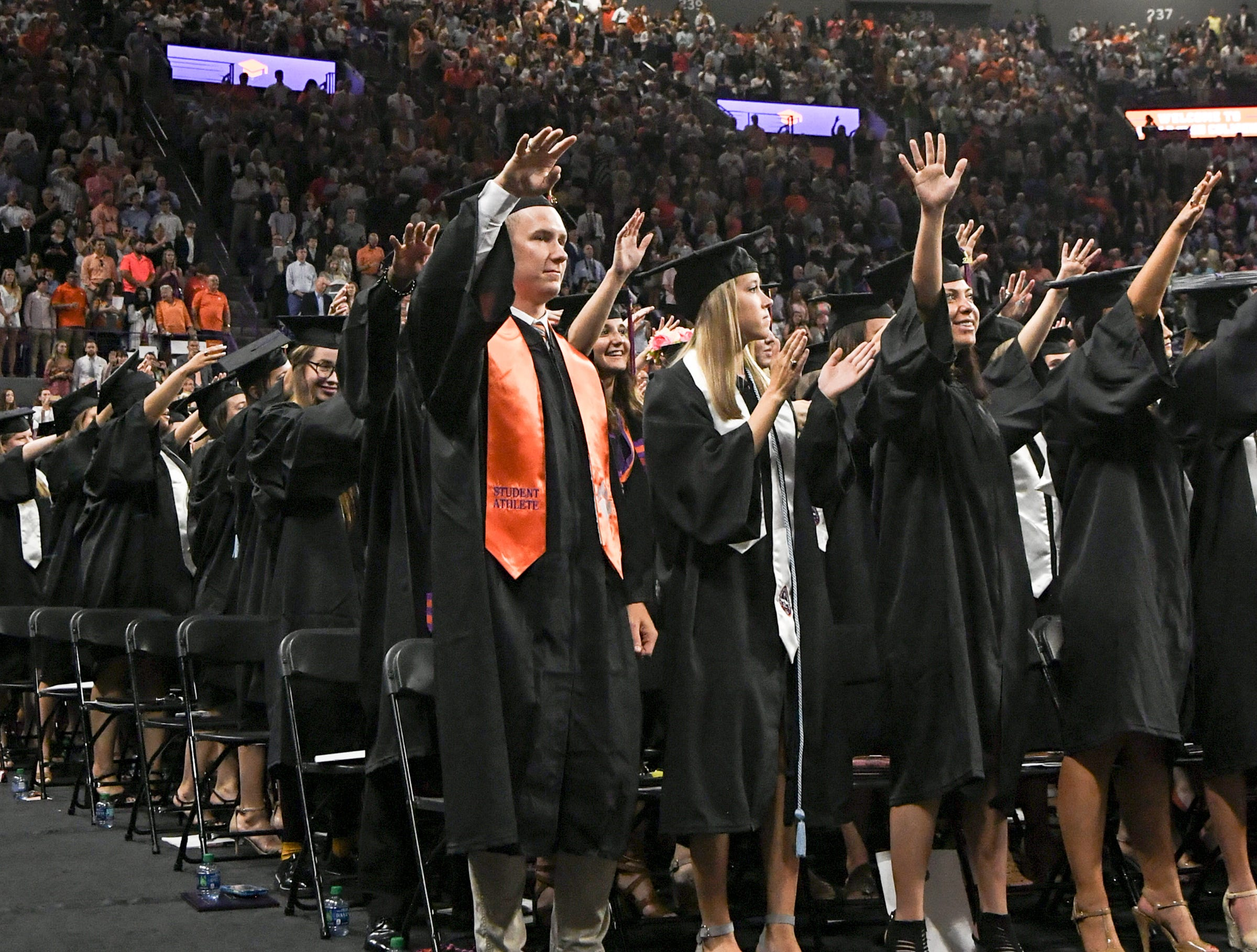 Ryan Mac Lain, a former football player, joins in waving for the alma mater after he earned his Bachelor of Arts in Psychology, during Clemson University commencement ceremonies in Littlejohn Coliseum in Clemson Friday, May 10, 2019.