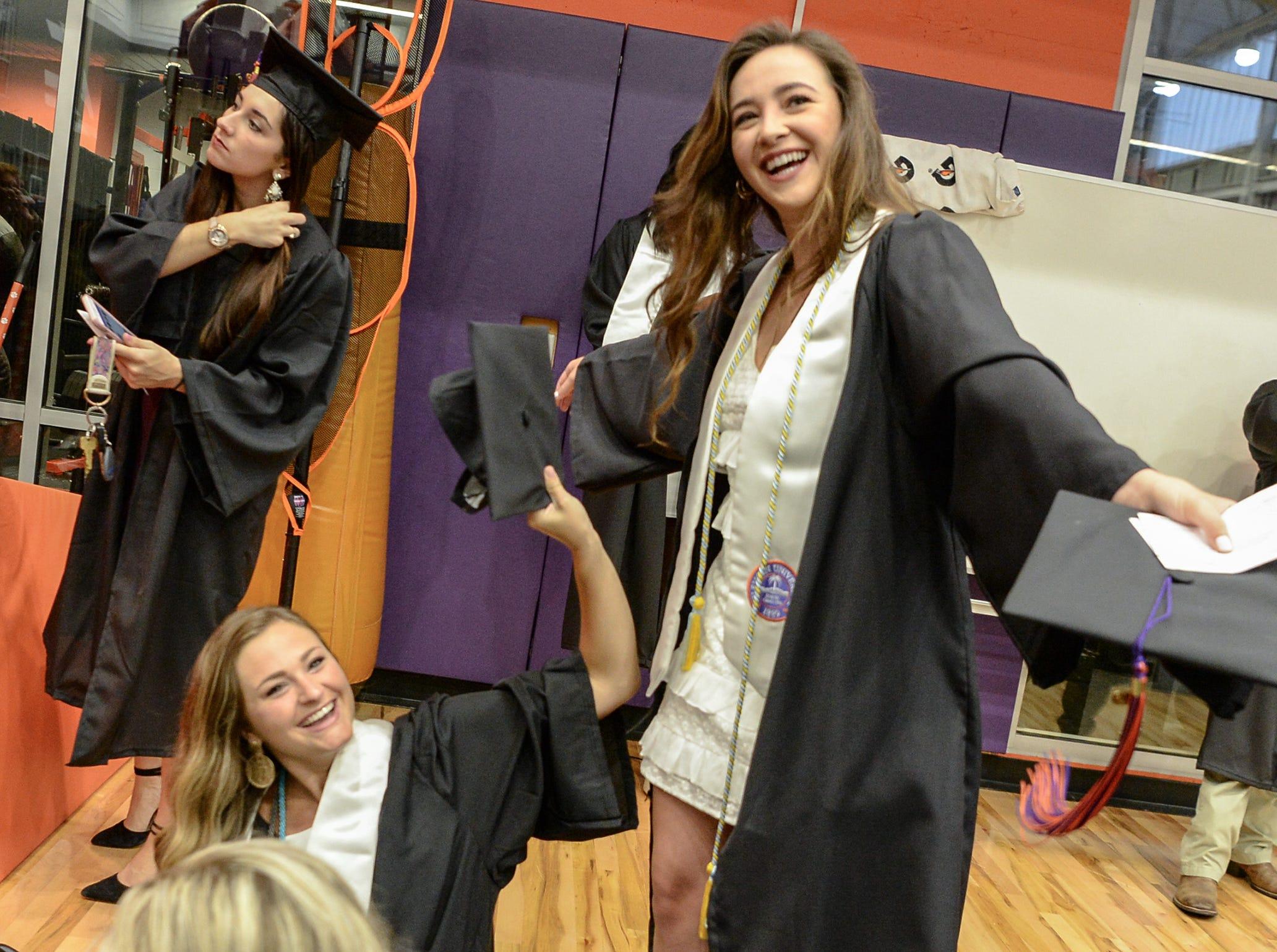 Emily Wessinger, left, cools off Jordan Kahn, right, with her cap before Clemson University commencement ceremonies in Littlejohn Coliseum in Clemson Friday, May 10, 2019.