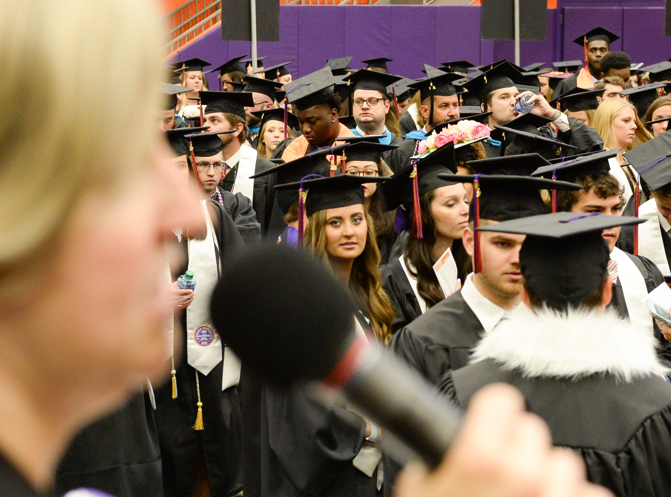Graduates look over toward Alanna Landreth, Assistant Director of Event Services, making an announcement before Clemson University commencement ceremonies in Littlejohn Coliseum in Clemson Friday, May 10, 2019.