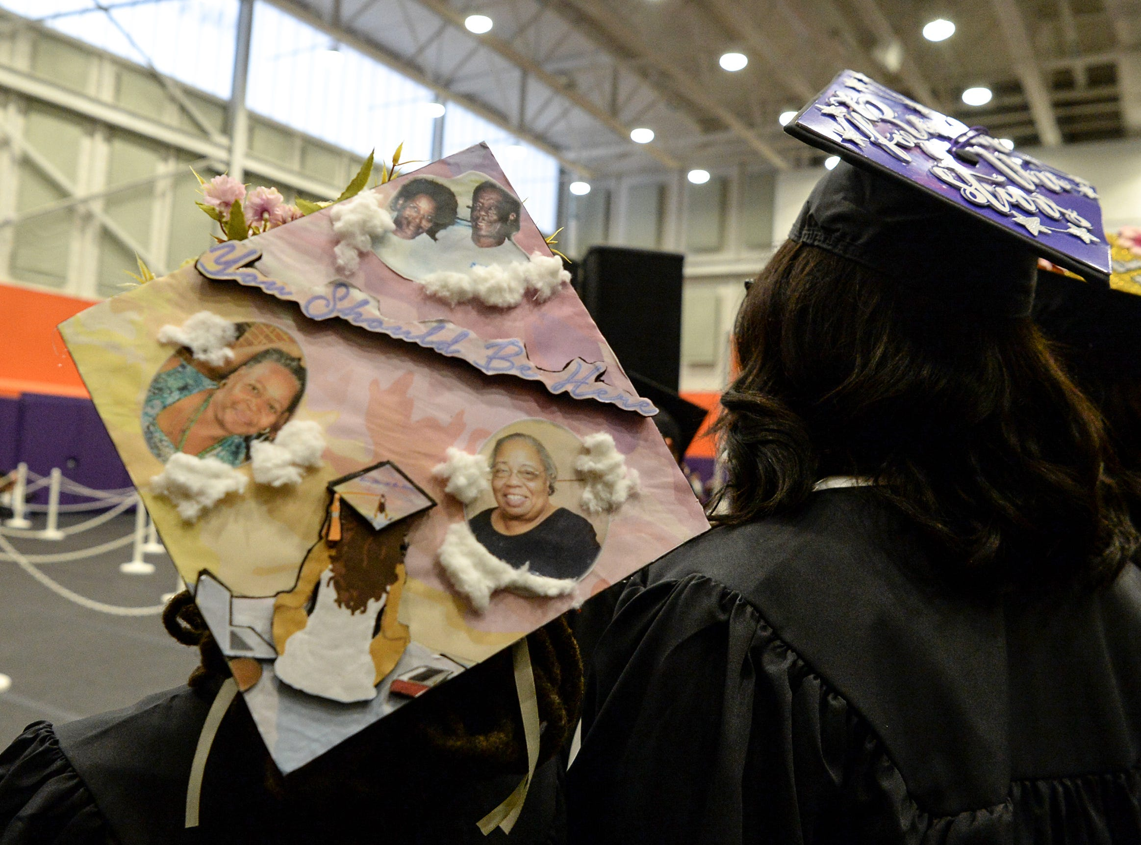 """Kendra Caldwell wears a cap with photos of late family members, during Clemson University commencement ceremonies in Littlejohn Coliseum in Clemson Friday, May 10, 2019. """"You should be here,"""" is written on the cap."""