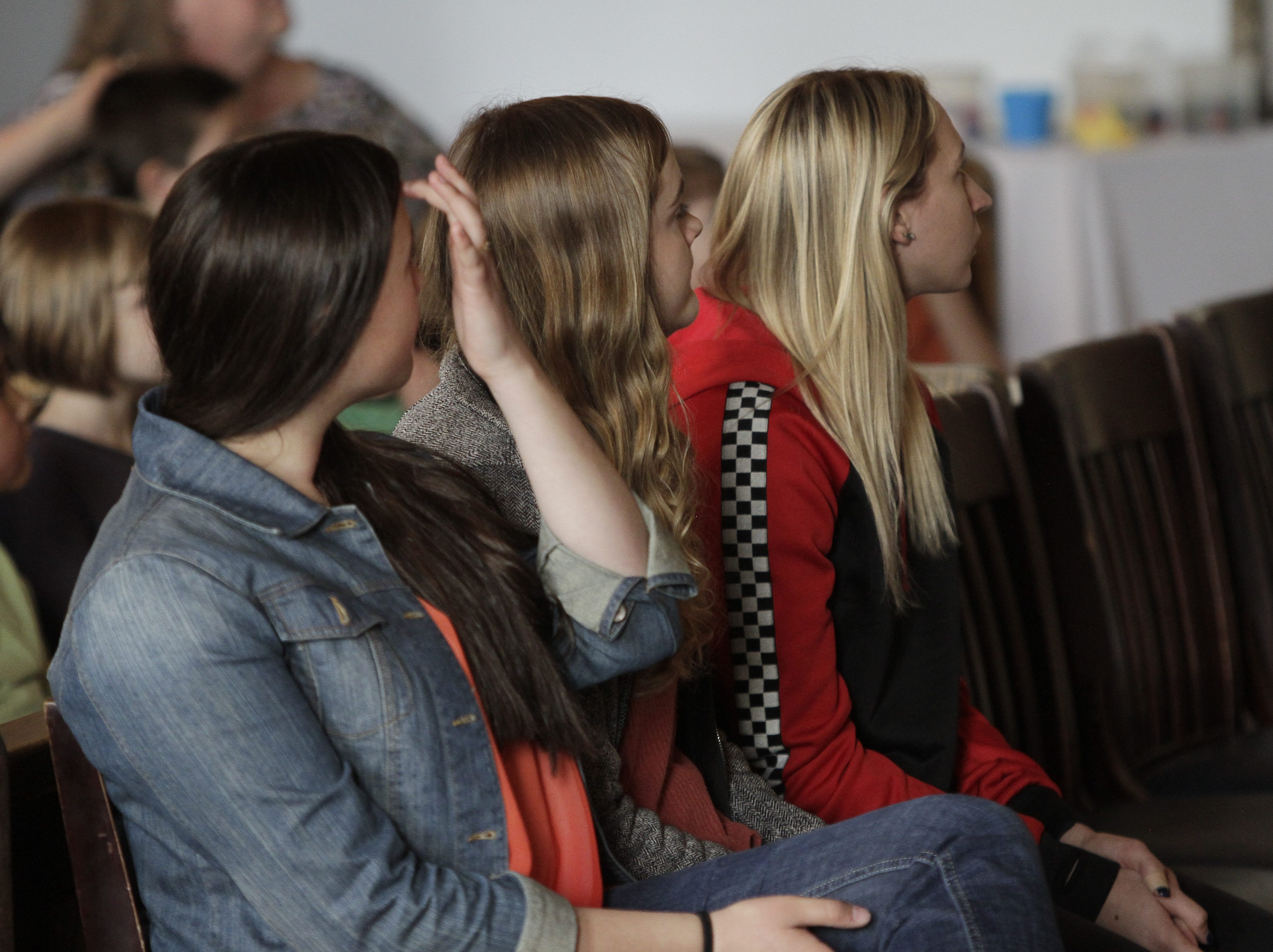 Raina Lindseth, Madison Johnson and Kenzie Houston watching their film as a part of the ceremony.