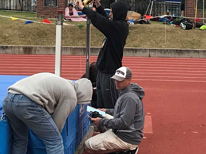 Belt track coach Jeff Graham (kneeling) checks the height of the high jump bar during the Districts 8C/10C track meet Friday at Memorial Stadium.