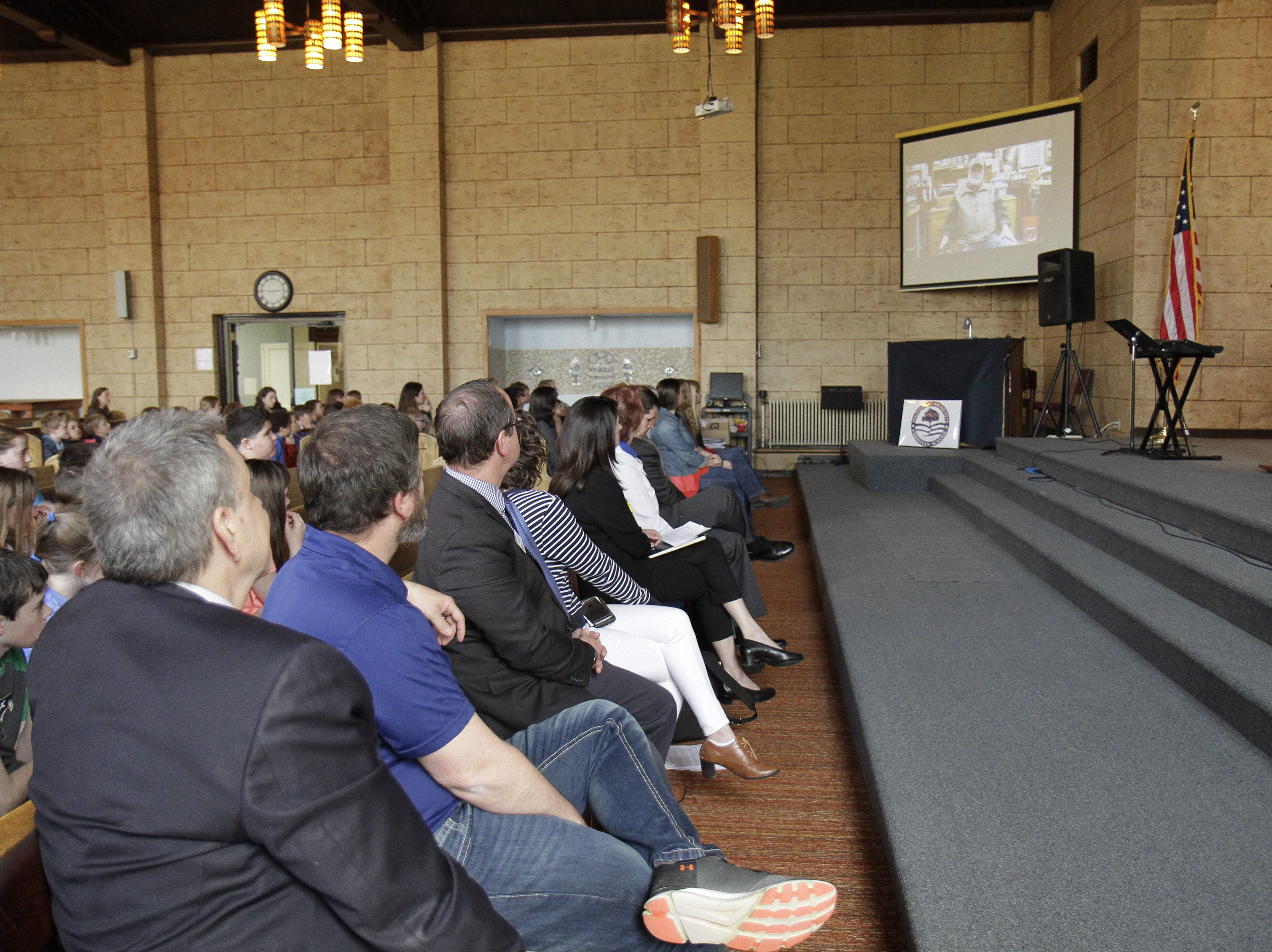 The school and city officials gathered to watch the documentary during the ceremony.