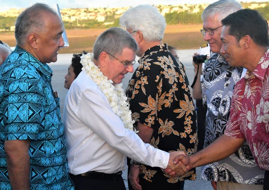 International Olympic Committee President Thomas Bach, in white, shakes hands with Tony Babauta, chief of staff for Gov. Lou Leon Guerrero while Bob Steffy, secretary general of Guam's National Olympic Committee waits his turn. At left is GNOC President Ricardo Blas.