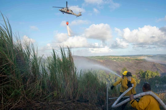 Guam Fire Department firefighters battle a blaze from the ground as Helicopter Sea Combat Squadron 25 provides a water drop in Santa Rita May 9.