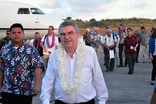 Wearing a fresh lei draped upon him moments before, International Olympic Committee President Thomas Bach heads to his motorcade after his arrival on the tarmac of the A.B. Won Pat Guam International Airport May 10.